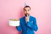 jóképű üzletember mutatja csend jel, miközben tartja születésnapi torta rózsaszín