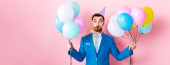 panoramic shot of businessman in party cap holding balloons on pink