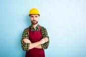 uražený dělník v bezpečnostní přilbě se zkříženýma rukama na modré