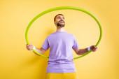 Tiefansicht eines fröhlichen Sportlers, der mit Hula-Hoop-Reifen auf Gelb trainiert