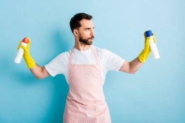 Serious bearded man holding spray bottles on blue stock vector