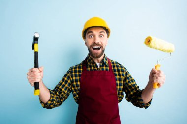 excited workman holding hammer and paint roller on blue