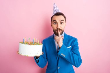 Handsome businessman showing hush sign while holding birthday cake on pink stock vector