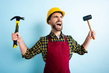 angry worker in safety helmet holding hammers on blue