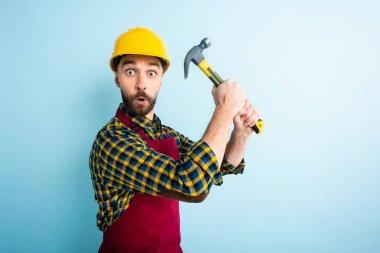 surprised workman in safety helmet holding hammer on blue
