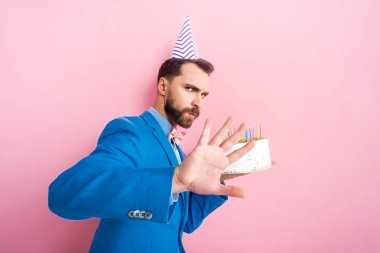 bearded man showing no gesture while holding birthday cake isolated on pink