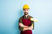 pozitivní pracovník v bezpečnostní přilbě drží váleček barvy na modré