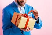 oříznutý pohled na vzrušeného muže v obleku dotýkajícího se stuhy na dárkové krabici izolované na růžové