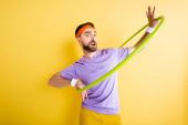 Verwirrter Sportler trainiert mit Hula-Hoop-Reifen auf Gelb