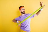 Verwirrter Sportler trainiert mit Hula-Hoop-Reifen in Gelb