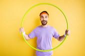 Glücklicher bärtiger Sportler mit Hula-Hoop-Reifen auf gelb