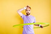 Müder Sportler trainiert mit Hula-Hoop-Reifen auf Gelb
