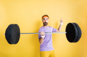 surprised sportsman pointing with finger and holding barbell on yellow
