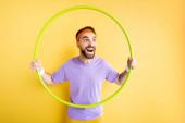 Aufgeregter Sportler mit Hula-Hoop-Reifen auf gelb