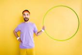 fröhlicher Sportler, der mit der Hand auf der Hüfte steht und Hula-Hoop-Reifen in Gelb hält
