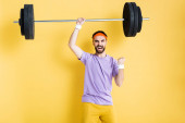 excited sportsman celebrating while working out with barbell on yellow