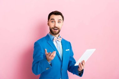 Cheerful bearded businessman holding digital tablet and gesturing on pink stock vector