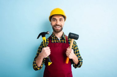 cheerful bearded workman holding hammers on blue