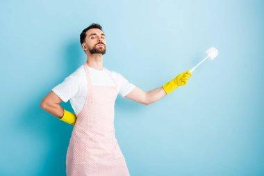 proud man in apron holding toilet brush on blue