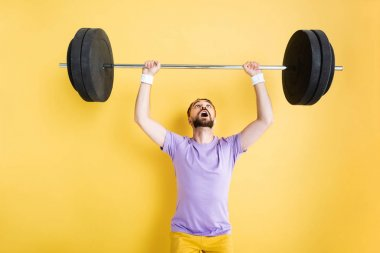 Surprised bearded sportsman looking at barbell while working out on yellow stock vector