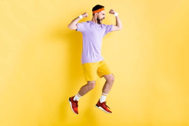 Side view of excited bearded sportsman jumping on yellow stock vector