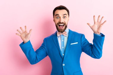 excited bearded businessman with opened mouth gesturing on pink