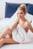attractive young woman sitting in bed in morning