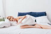 mosolygó nő feküdt ágyneműben reggel