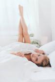 krásná usmívající se žena ležící s nohama v prostěradlech na posteli v dopoledních hodinách
