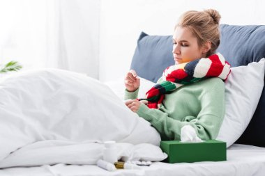 sick woman in scarf having fever and looking at thermometer in bed