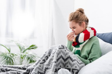 Sad ill woman in scarf having runny nose in bed with napkins stock vector