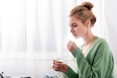 ill woman taking pills and holding glass of water in bedroom