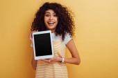 veselé bi-rasové děvče ukazující digitální tablet s prázdnou obrazovkou na žlutém pozadí
