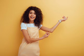 cheerful bi-racial girl pointing with hands while smiling at camera on yellow background