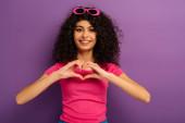 boldog bi-rasszista lány mutató szív jel a kezét, miközben a kamera lila háttér