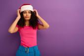 skeptický bi-rasové dívka dotýká Santa klobouk a odvrací pohled na fialové pozadí