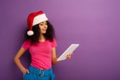 usmívající se bi-rasová dívka v santa klobouk pomocí digitální tablet na fialovém pozadí