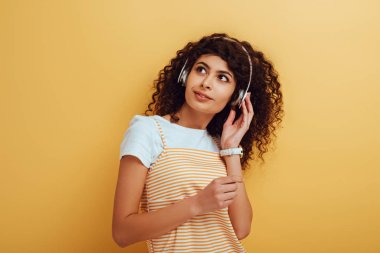 dreamy, positive mixed race girl in wireless headphones looking away on yellow background