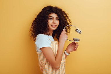 smiling mixed race girl looking away while holding wireless headphones on yellow background