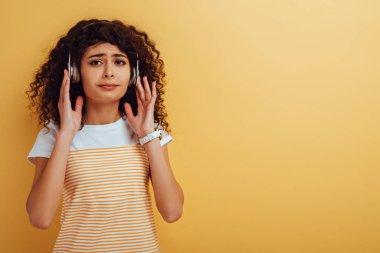 upset bi-racial girl listening music in headphones on yellow background