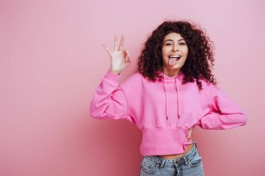 Cheerful bi-racial girl sticking out tongue and showing okay gesture on pink background stock vector