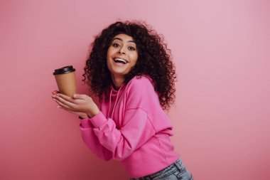 Happy bi-racial girl smiling at camera while holding coffee to go on pink background stock vector