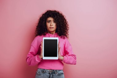 Disappointed bi-racial girl looking at camera while showing digital tablet with blank screen on pink background stock vector