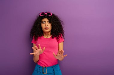 scared bi-racial girl showing stop gesture while looking at camera on purple background