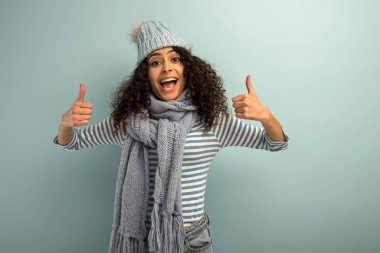 Cheerful bi-racial girl in warm hat and scarf showing thumbs up while looking at camera on grey background stock vector