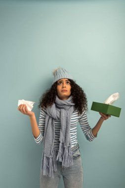 Diseased bi-racial girl in warm hat and scarf looking up while holding paper napkins on grey background stock vector
