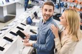 usmívající se přítel drží nový smartphone a mluvit s přítelkyní v obchodě domácí spotřebiče