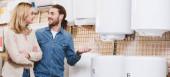 panoramatický záběr usmívající přítel a přítelkyně mluví v blízkosti kotle v obchodě domácí spotřebiče
