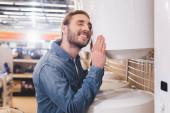 Lächelnder Mann mit geschlossenen Augen berührt Heizkessel in Haushaltsgerätehaus