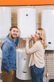 Lächelnder Freund und Freundin zeigen mit Fingern auf Boiler im Haushaltsgerätehaus